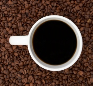 Cup of coffee in a sea of coffee beans